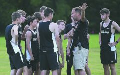 Harlan County cross country and track coach Ryan Vitatoe talked with his team during a meet last fall. The HCHS programs have been moved to 2A starting with the 2020-2021 school year, according to the Kentucky High School Athletic Association.