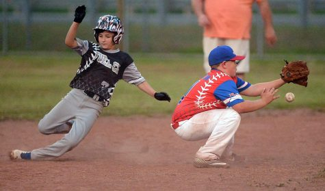 Tristan McMillian, of Fuelco, swiped second base Tuesday as Grant Shelton took the throw in Harlan Little League play at Huff Park.