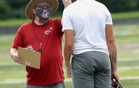 Harlan County assistant coach Chad Wood checked the temperature of freshman Tyler Baker before practice on Thursday as part of the precautions to keep the players safe during the coronavirus pandemic.
