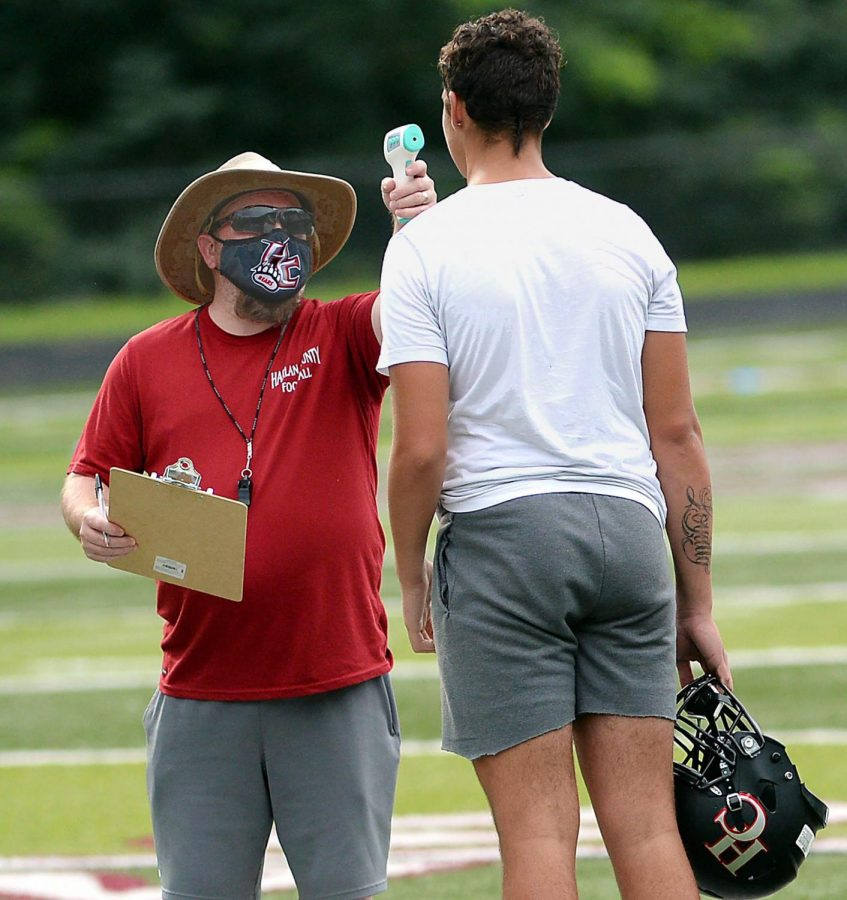 Harlan+County+assistant+coach+Chad+Wood+checked+the+temperature+of+freshman+Tyler+Baker+before+practice+on+Thursday+as+part+of+the+precautions+to+keep+the+players+safe+during+the+coronavirus+pandemic.