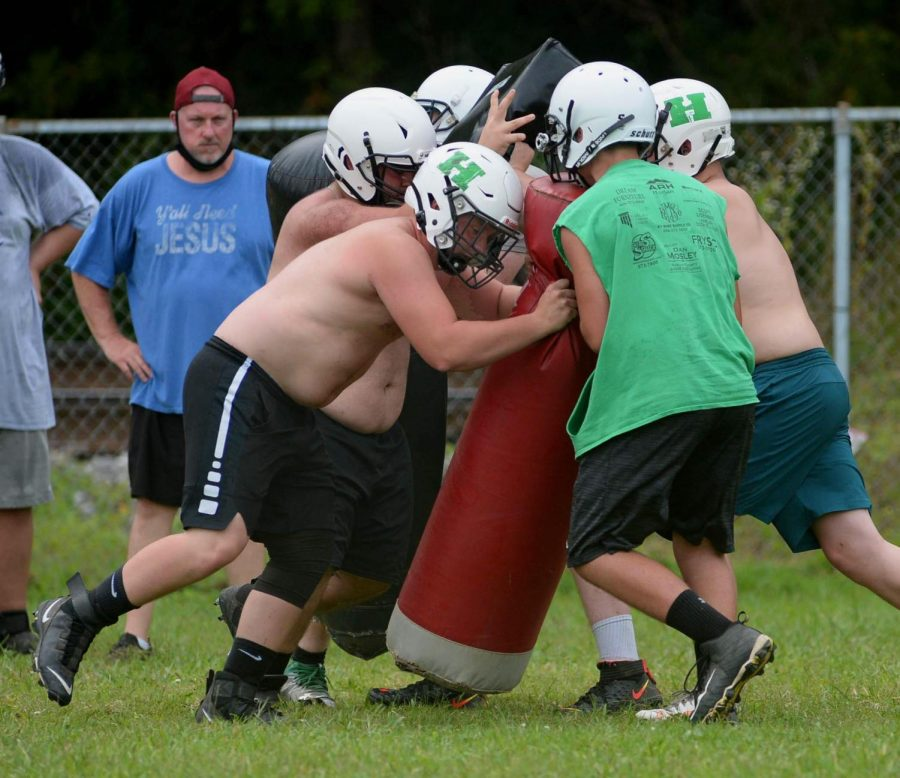 Harlan+linemen+worked+on+a+drill+with+assistant+coach+Joe+Bill+Baker+during+a+recent+practice+session.
