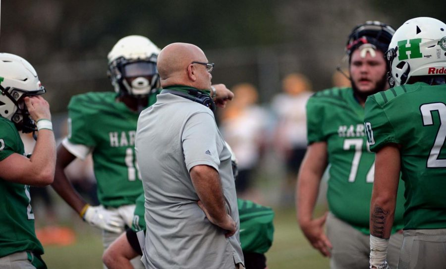 Harlan+coach+Eric+Perry+talked+with+his+team+during+a+game+earlier+this+season.+The+Green+Dragons+earned+their+first+win+with+a+29-18+victory+Friday+at+East+Ridge.