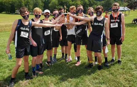The Harlan County Black Bears are pictured with their trophy after placing second in the season-opening meet Saturday at Lynn Camp. The HCHS girls also placed second.