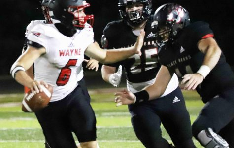 Josh Turner and Hunter Helton pressured Wayne County quarterback Brody Weaver during Friday's game at Coal Miners Memorial Stadium. Weaver passed for 115 yards and ran for 113 in the Cardinals' 42-0 win.