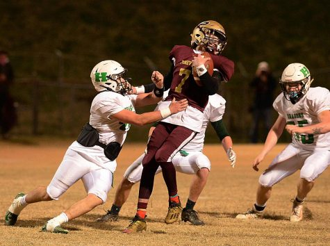 Several Green Dragons brought down Pineville quarterback Reese Capps in first-round playoff action Friday. The Harlan defense had a safety and scored a touchdown off a fumble in the first half to build a 14-7 lead. The Lions rallied for a 21-14 victory.