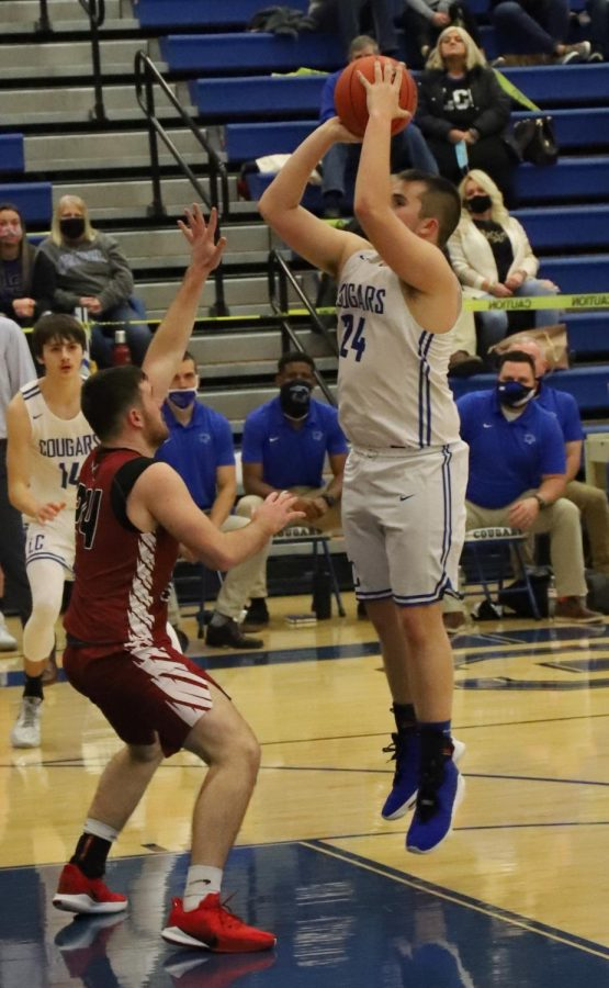 Letcher Central senior forward Joby Johnson put up a shot over Harlan County's Josh Turner in Saturday's game. Johnson scored five points in the Cougars' 55-35 loss.
