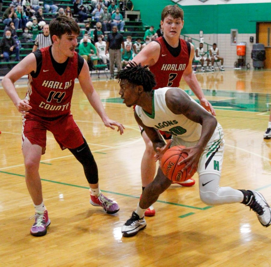 Harlan guard Jordan Akal looked for an opening against Harlan County's Tyler Cole and Trent Noah in Friday's district clash. Akal scored 35 as the Dragons rolled to a 74-50 win.