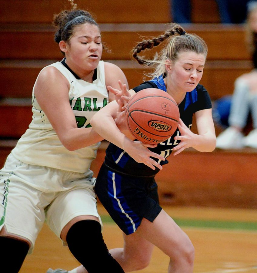 Harlan freshman Aymanni Wynn battled with Bell County's Abby Cornett for a loose ball in 52nd DIstrict Tournament action Monday against Bell County. The Lady Cats rallied in the second half for a 58-39 victory.