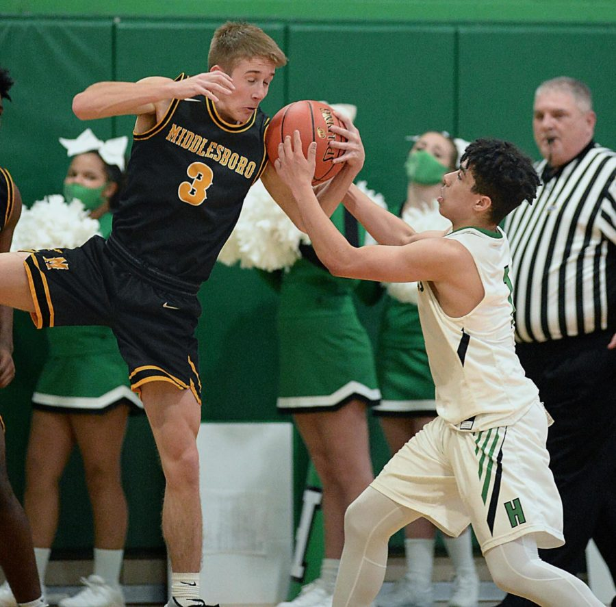 Middlesboro's Ethan Barton and Harlan's Kyler McLendon battled for possession of the ball in 52nd DIstrict Tournament action Tuesday. McLendon scored 17 points as the Dragons advanced with a 66-58 victory.