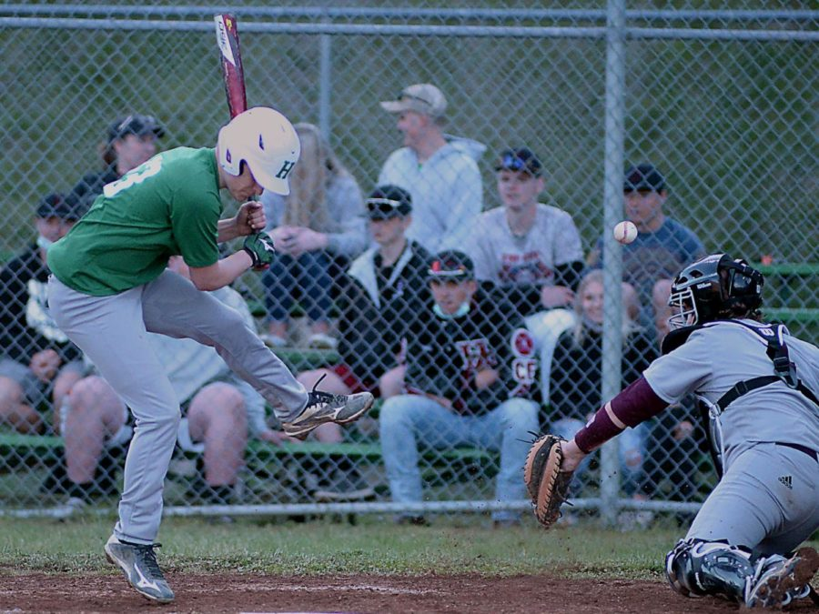 Harlan's Shane Lindsey jumped out of the way of a pitch as Pineville catcher Wyatt Caldwell stretched to make the stop in the season opener for both teams Monday. Pineville rallied for a 12-6 victory.