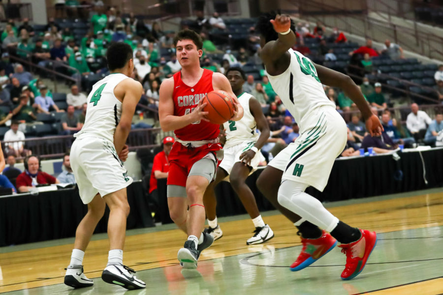 Corbin forward Brody Wells drove to the basket in 13th Region Tournament as Harlan's Kaleb McLendon and Jordan Akal defended. Wells scored 15 points in the Redhounds' 63-53 win.