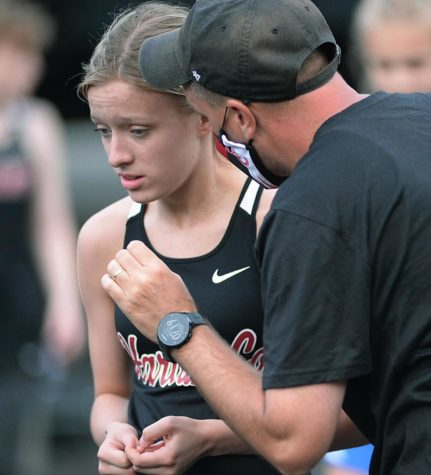 Harlan County coach Ryan Vitatoe talked with eighth-grader Peyton Lunsford on Friday in the Coal Miners Invitational. Lunsford set a school record in winning the 1,600-meter run.