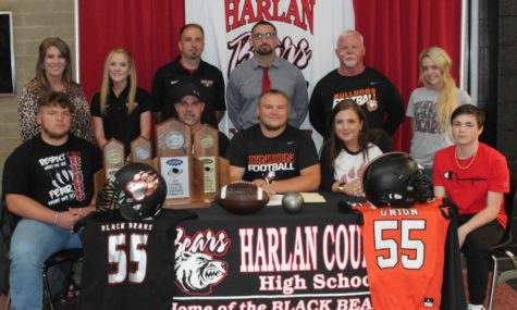 Hunter Blevins signed Thursday to continue his football and track career at Union College in a ceremony at Harlan County High School. Those pictured at the signing included, from left, front row: Connor Blevins, Scotty Howard, Blevins, Chandra Howard and Tye Howard; back row: Harlan County High School Principal Kathy Minor, HCHS assistant track coach Arynn Johnson, HCHS track coach Ryan Vitatoe, HCHS football coach Eddie Creech, Union College football coach John Luttrell and Morgan Grace.