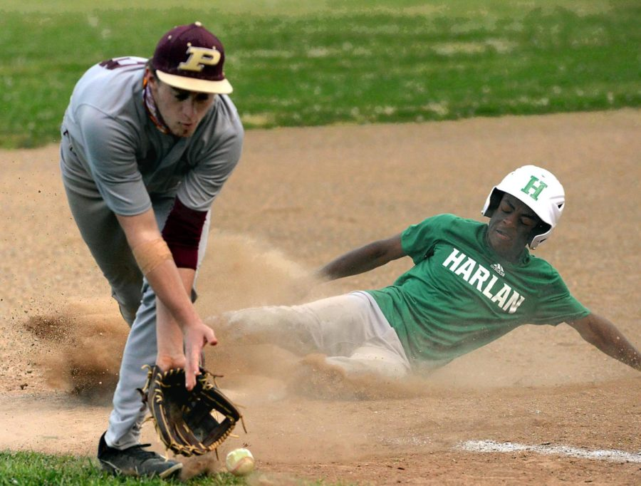 Harlan's Trey Barnes was safe on a slide into third base as Pineville's Evan Biliter fielded the throw in Thursday's game. The Dragons won 5-2.