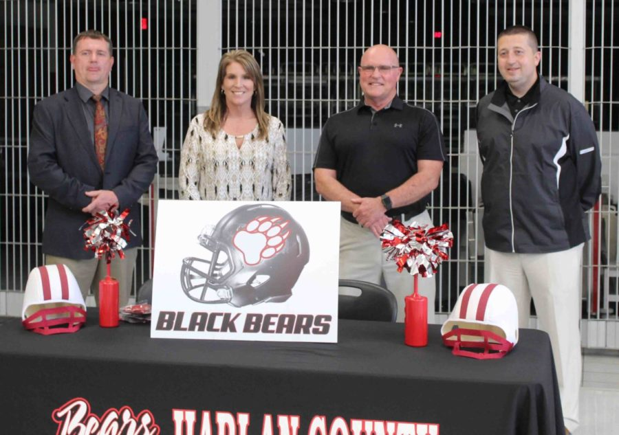 Harlan County Schools Superintendent Brent Roark (left), HCHS Principal Kathy Minor and athletic director Eugene Farmer (right) are pictured with new HCHS football coach Amos McCreary just after he met with players on Tuesday at the school.