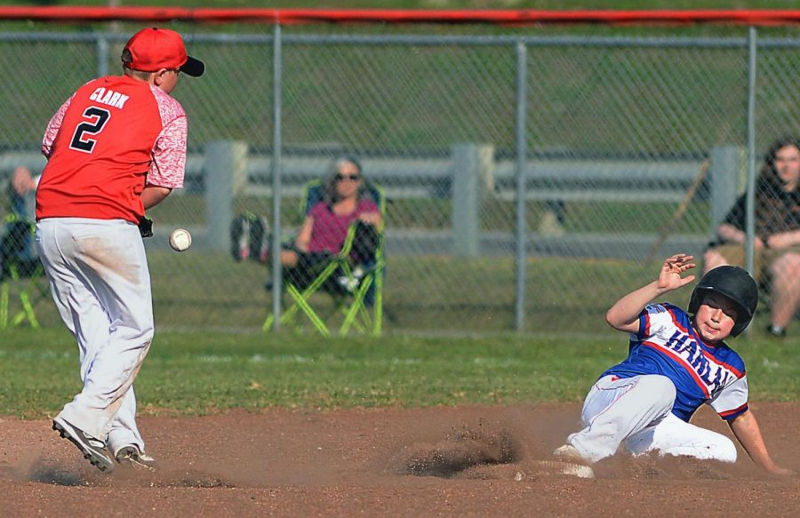 Harlan's Cameron Brock slid into second base as Tri-City shortstop Carson Clark fielded the throw in Area 4 Tournament action Friday. The Harlan All-Stars advanced to the tournament finals with an 11-1 victory.