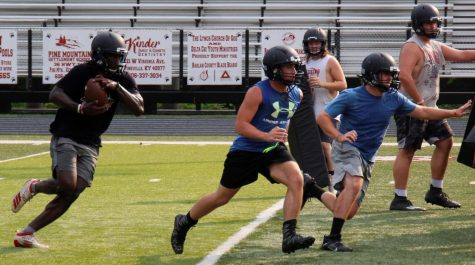 Demarco Hopkins followed Luke Carr (left) and Isaac Downs during a practice session Tuesday at Coal Miners Memorial Stadium.