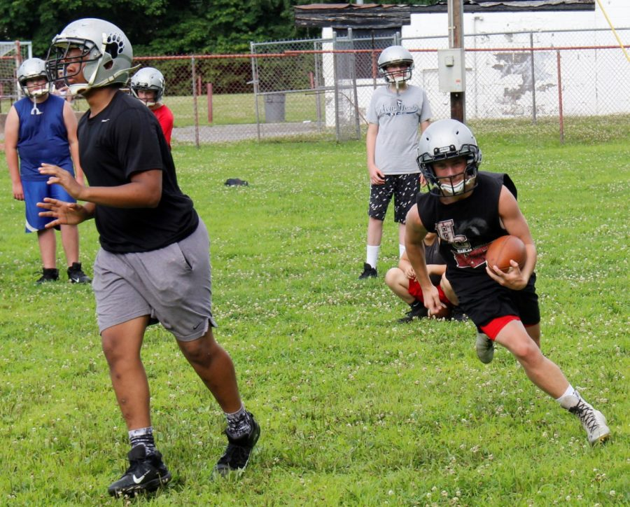 Jayce Brown followed a block from Shemar Carr in Harlan County's eighth-grade football practice on Monday.