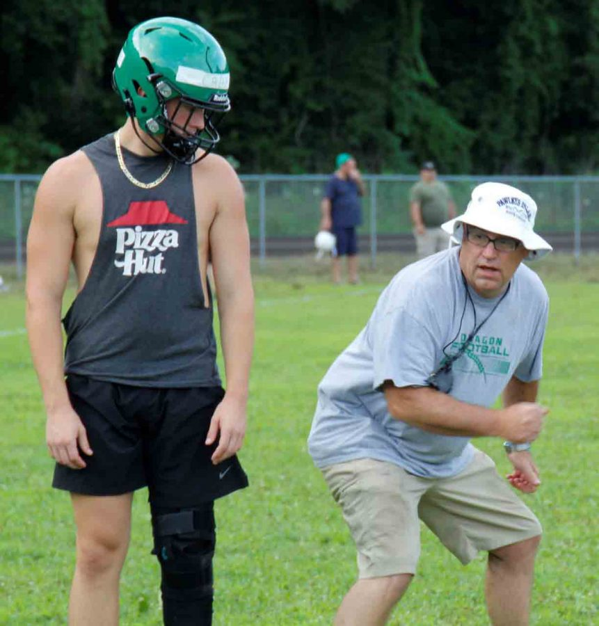 Harlan coach Eric Perry talked with quarterback Cade Middleton during a practice session Tuesday. The Green Dragons open their season Aug. 20 at Berea.