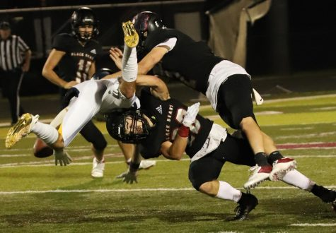 Two Harlan Couty defenders converged for a tackle earlier this season. The Black Bears open their disrict schedule Monday at Clay County.