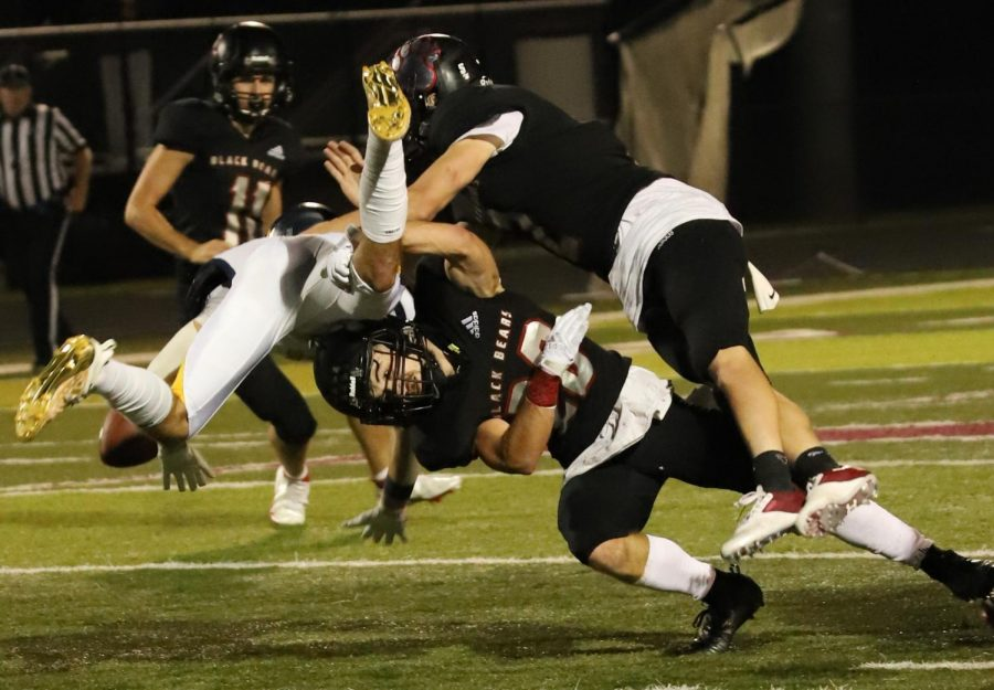Two+Harlan+Couty+defenders+converged+for+a+tackle+earlier+this+season.+The+Black+Bears+open+their+disrict+schedule+Monday+at+Clay+County.